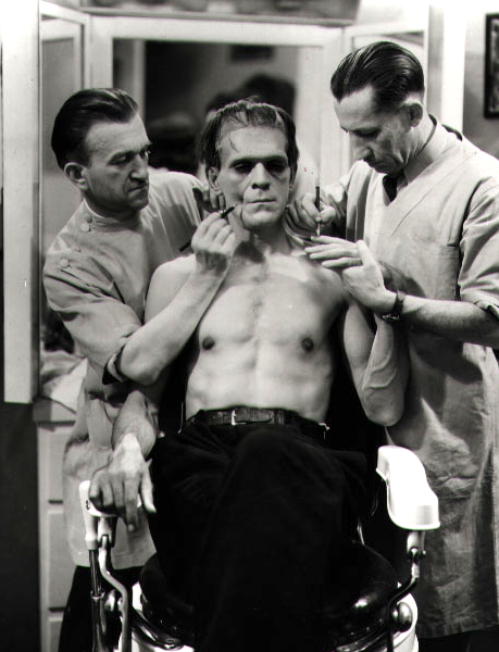 """""""Just hold still, we're almost done here,"""" Jack Pierce and assistant as Dr. Garramone and assistant. Boris Karloff as Transman."""